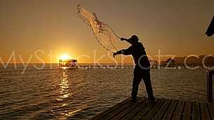 Cast Net from a dock at sunset
